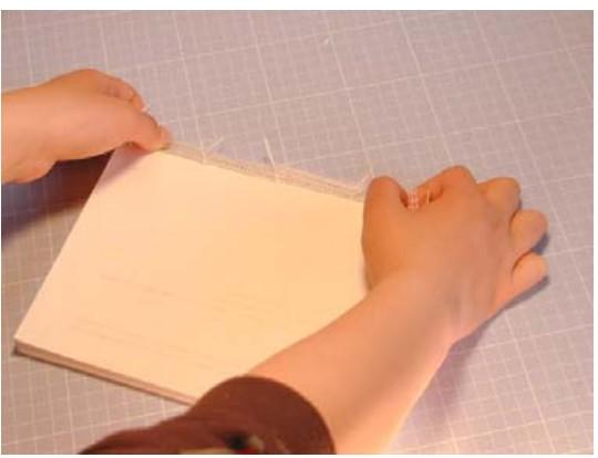 次に、固定していたものを外し、糸と補強布を外側に折ります。