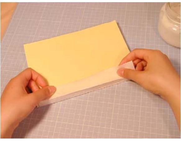 背表紙にノリを塗った上から補強紙を貼ります。
