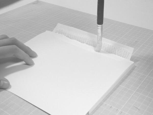 貼り付けた見返し用紙の上に、糸、不織布、補強紙を貼り付けます。