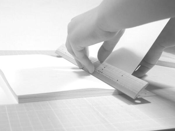 乾かないうちに見返し用紙の内側の折り目を定規ではさみ、もう一度折り目をつけます。