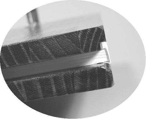 拡大写真のようにこの板は、締め付け用に作成したものです。背の部分を挟む面に溝を作ってあります。