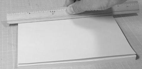 見返し用紙をはったところに補強紙を戻してはり付けます。上から強く押さえて十分に接着してください。定規などを使うと押さえやすいと思います。